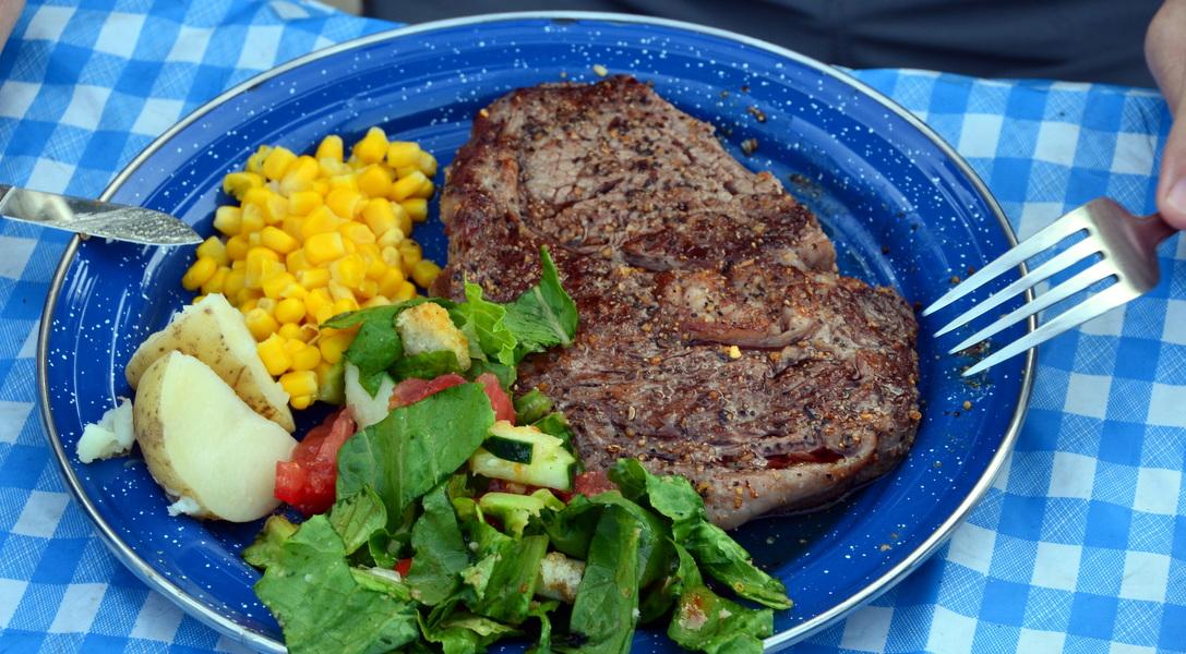 Maine Ribeye steak, corn, potatoes, salad, dinner on canoe trip